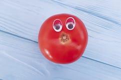 Tomato funny organic eyes cartoon on blue wooden positive emotion. Tomato eyes funny organic cartoon on blue wooden emotion Stock Photography