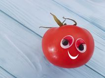 Tomato funny organic person eyes cartoon on blue wooden positive emotion. Tomato eyes funny organic cartoon on blue wooden emotion person Royalty Free Stock Images