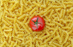 Tomato with fusilli pasta as background Royalty Free Stock Photos