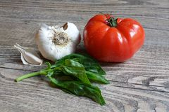 Tomato, Garlic and Basic on Wood Table Stock Photos