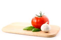 Tomato, Garlic and Basil on cutting board. Wooden Cutting Board with healthy ingredients on white background Royalty Free Stock Photography