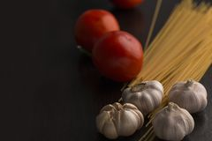 Tomato, garlic and raw spaghetti on black wood.Copy space. stock photos