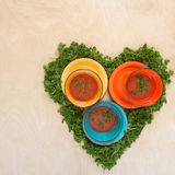 Tomato gazpacho soup in colored bowls next to a heart symbol Stock Photography