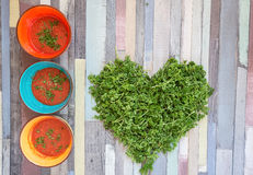 Tomato gazpacho soup in colored bowls on a wooden table Royalty Free Stock Photo