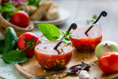 Tomato gazpacho soup in two glass cups. Tomato gazpacho soup with fresh cucumbers, red pepper, green basil, onions Stock Photo