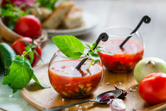 Tomato gazpacho soup in two glass cups. Tomato gazpacho soup with fresh cucumbers, red pepper, green basil, onions Royalty Free Stock Photos