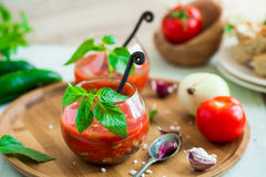 Tomato gazpacho soup in two glass cups. Tomato gazpacho soup with fresh cucumbers, red pepper, green basil, onions Royalty Free Stock Image