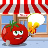 Tomato giving you a gift box in front of a storefront with speech bubble Stock Image