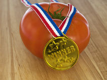 Tomato with a gold medal Royalty Free Stock Images