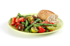 Tomato and Green Bean Salad. Plate of tomato and green bean salad with a piece of grain bread Royalty Free Stock Photo
