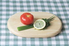Tomato, green onion and lemon on cutting Board Stock Photos