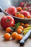 Tomato Harvest. Of red and orange cherry tomatoes, some tomatoes in a colander Stock Photos