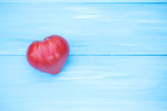 Tomato heart on a blue table. Royalty Free Stock Photos