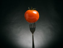 Tomato impaled on fork Stock Images