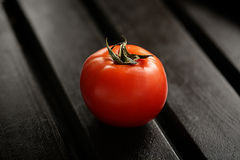 Tomato isolated on black wood backgroound. Lifestyle healthy eating Food photo concept. Stock Image