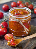 Tomato jam. With pepper and garlic in wooden spoon. Selective focus, shallow doff Royalty Free Stock Image
