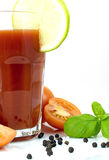 Tomato juice. In a large tumbler decorated with a lime slice, pepper, salt, tomatoes and basil Stock Photo
