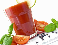 Tomato juice. In a large tumbler decorated with a lime slice, salt, pepper, tomatoes and basil Stock Photo
