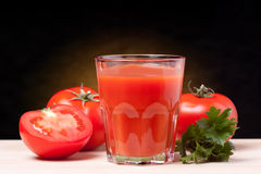 Tomato juice. Fresh tomatoes and a glass full of tomato juice Royalty Free Stock Image