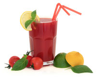Tomato Juice. In a glass with lemon, lime, tomatoes and basil herb leaf over white background Stock Photos