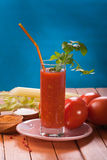Tomato juice. With celery on blue background royalty free stock image