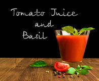 Tomato juice with basil on blackboard Stock Photos