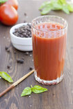 Tomato juice. And basil, wooden table and papper royalty free stock images