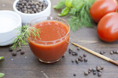 Tomato juice. And basil, wooden table and papper royalty free stock photos