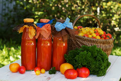 Tomato juice in a bottle. Tomato juice with parsley in a bottle on wooden table, horizontally, rustic Stock Photo