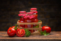 Tomato juice. Bottles of tomato juice in crate on wooden table Stock Images