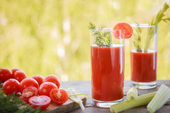 Tomato juice in clear glass on wooden table Royalty Free Stock Image