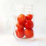 Tomato juice, drink, smoothie in a glass concept. Plum tomatoes. In a transparent jar mug on white. Many small fresh red vegetables in a cup stock image