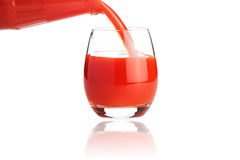 Tomato juice is flowing into a glass isolated on white Stock Photos