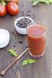 Tomato juice. Fresh tomato juice, herbs and spices on wooden table royalty free stock photography