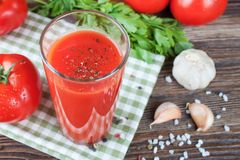 Tomato juice and fresh tomatoes on wooden table royalty free stock image