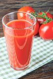 Tomato juice and fresh tomatoes on wooden table royalty free stock photos