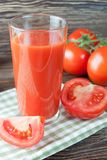 Tomato juice and fresh tomatoes on wooden table stock photos