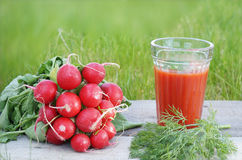 Tomato juice with fresh vegetables on wooden table. Royalty Free Stock Images