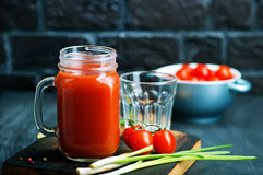 Tomato juice. In glass bank and on a table Royalty Free Stock Images