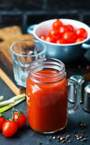 Tomato juice. In glass bank and on a table Royalty Free Stock Photos