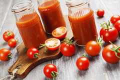 Tomato juice. In a glass bottle on a wooden table Royalty Free Stock Photography