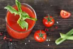 Tomato juice in glass with celery. Cherry tomato and spices, top view Stock Image