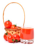 Tomato juice in glass, cherry tomatoes in the basket Stock Photos