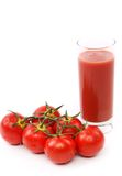 Tomato juice in glass with a cluster of tomatoes Royalty Free Stock Photography