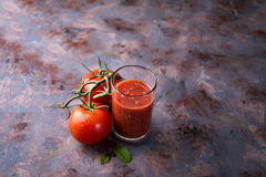 Tomato juice in glass. And fresh tomatoes on stone background copy space Stock Photos