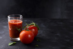 Tomato juice in glass. And fresh tomatoes on stone black background, copy space Royalty Free Stock Images