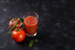 Tomato juice in glass. And fresh tomatoes on stone black background, copy space Royalty Free Stock Photos
