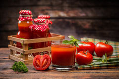 Tomato juice. In glass and fresh tomatoes on vintage wooden board Royalty Free Stock Images