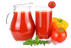 Tomato juice in glass jug with tomato, garlic, spices, and basil isolated on white background Stock Images