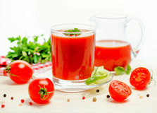 Tomato juice in glass, jug with greenery, basil, cutted tomato f Royalty Free Stock Photo